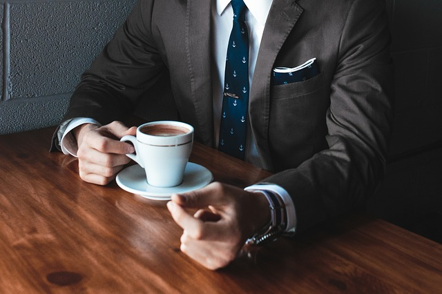image of a man in suit drinking coffee